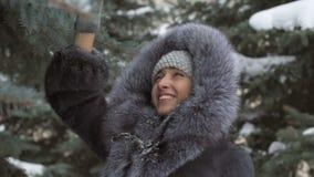 Menina para agitar a neve dos ramos A neve nas árvores video estoque