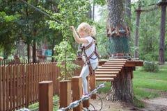 A menina passa um obstáculo no parque da corda imagem de stock
