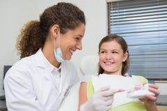 A menina pediatra do dentista mostrando como escovar seus dentes Imagem de Stock Royalty Free