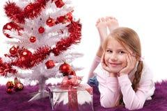 Menina pela árvore bonita do xmas do branco Fotografia de Stock Royalty Free
