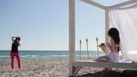 A menina pelo mar, de bastidores, fotógrafo da foto trabalha, fêmea com as ondas no bungalow, exoticism, pano branco, vento torna filme