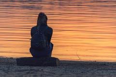 Menina pelo rio no por do sol fotografia de stock royalty free