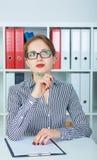 Menina pensativa bonita que senta-se no escritório que prepara-se para escrever o resumo Imagem de Stock