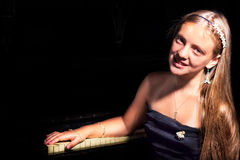 Menina pensativa bonita que senta-se perto do piano em um fundo escuro Foto de Stock Royalty Free
