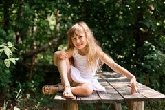 Menina pensativa consideravelmente de sorriso que senta-se na ponte velha Fotografia de Stock Royalty Free