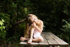 Menina pensativa consideravelmente de sorriso que senta-se na ponte velha Fotos de Stock Royalty Free