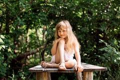 Menina pensativa consideravelmente de sorriso que senta-se na ponte velha Foto de Stock Royalty Free