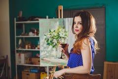 A menina pensativa criativa do pintor pinta uma imagem colorida no canva Fotos de Stock Royalty Free