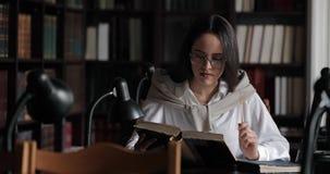 Menina pensativa que estuda na biblioteca vídeos de arquivo