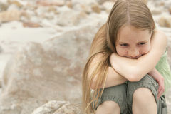 Menina pensativa que senta-se na rocha Foto de Stock Royalty Free
