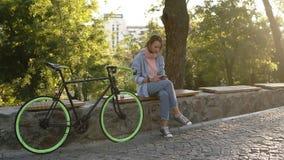 Menina pensativa que senta-se no banco no parque da cidade com sua bicicleta trekking ao lado dela Olhando seu móvel, vestindo video estoque