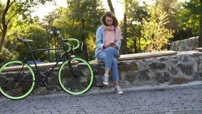 Menina pensativa que senta-se no banco no parque da cidade com sua bicicleta trekking ao lado dela Olhando seu móvel, vestindo filme