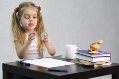 A menina pensativamente e gira effortlessly o globo de vidro, sentando-se na tabela na imagem do escritor Fotos de Stock Royalty Free