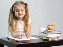 A menina pensativamente e gira effortlessly o globo de vidro, sentando-se na tabela na imagem do escritor Fotos de Stock