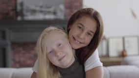 Menina pequena adorável do albino do retrato que abraça sua amiga que olha o sorriso da câmera Conceito da amizade carefree filme