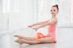 Menina pequena bonita da ginasta no vestido cor-de-rosa do sportswear, elemento da ginástica das artes de palco com a bola na cla fotografia de stock