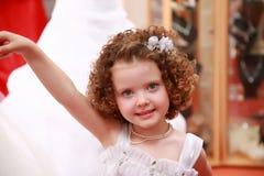 Menina pequena, bonita em um vestido das meninas brancas. Foto de Stock