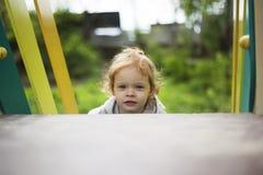 A menina pequena bonita feliz do ruivo escala a corredi?a no campo de jogos imagem de stock royalty free