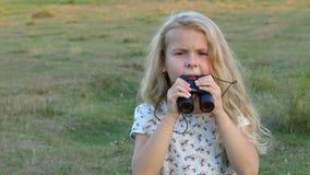 Menina pequena bonita que olha através dos binóculos A criança bonita está guardando um par de binóculos video estoque