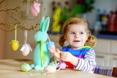 Menina pequena bonito da crian?a que decora a ?rvore e o coelho com os ovos pl?sticos pasteis coloridos Crian?a feliz do beb? que fotos de stock