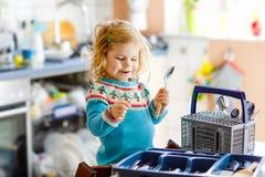 Menina pequena bonito da crian?a que ajuda na cozinha com m?quina de lavar do prato Crian?a loura saud?vel feliz que classifica f fotos de stock