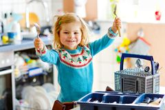 Menina pequena bonito da crian?a que ajuda na cozinha com m?quina de lavar do prato Crian?a loura saud?vel feliz que classifica f imagem de stock royalty free