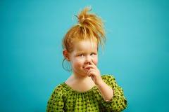 A menina pequena bonito do ruivo escolhe seu nariz com o dedo no azul isolado imagem de stock royalty free