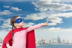 Menina pequena bonito do super-herói no casaco vermelho fotografia de stock