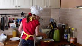A menina pequena bonito faz o jantar A menina pequena prepara o alimento na cozinha Menina bonito vestida como um cozinheiro chef vídeos de arquivo