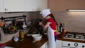 A menina pequena bonito faz o jantar A menina pequena prepara o alimento na cozinha Menina bonito vestida como um cozinheiro chef video estoque