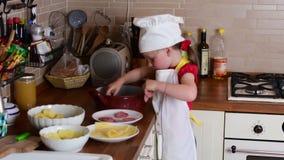 A menina pequena bonito faz o jantar A menina pequena prepara o alimento na cozinha Menina bonito vestida como um cozinheiro chef filme