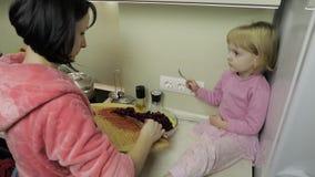 Menina pequena bonito que cozinha com sua mãe Pouco filha com mãe junto video estoque