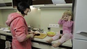 Menina pequena bonito que cozinha com sua mãe Pouco filha com mãe junto filme