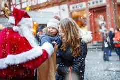 Menina pequena da criança com a mãe no mercado do Natal Foto de Stock Royalty Free