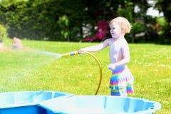 Menina pequena da criança que joga com a mangueira da água no jardim Imagens de Stock Royalty Free
