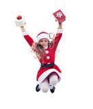 Menina pequena de Papai Noel que salta altamente com presentes Foto de Stock