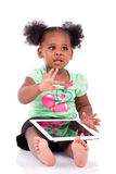 Menina pequena do americano africano que usa um PC da tabuleta Imagens de Stock Royalty Free