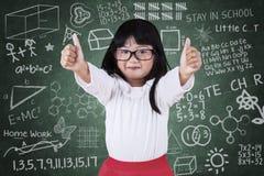 Menina pequena do estudante com polegares acima Foto de Stock