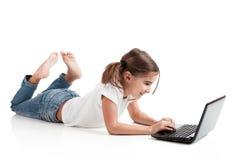 Menina pequena do estudante com um portátil imagens de stock royalty free