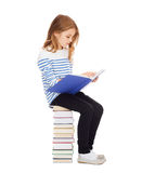 Menina pequena do estudante que senta-se na pilha de livros Fotos de Stock Royalty Free
