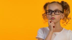 Menina pequena do lerdo nos monóculos que pensa sobre a decisão da tarefa ou a carreira futura filme