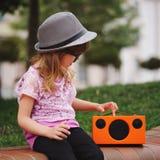 A menina pequena do moderno escuta música no spea de vista retro sem fio Foto de Stock