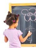 A menina pequena do mulato desenha na placa Fotos de Stock Royalty Free