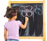 A menina pequena do mulato desenha na placa Imagem de Stock