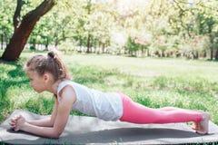 A menina pequena e magro está estando na posição da prancha Está olhando direta A menina cincentrated no exercício Imagens de Stock