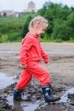 Menina pequena e positiva que joga perto das poças Imagem de Stock