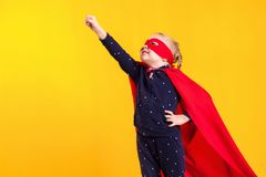 Menina pequena engraçada da criança do super-herói do poder em uma capa de chuva vermelha e em uma máscara Conceito do super-heró Fotografia de Stock Royalty Free