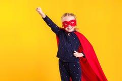 Menina pequena engraçada da criança do super-herói do poder em uma capa de chuva vermelha e em uma máscara Conceito do super-heró Imagens de Stock Royalty Free