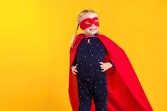 Menina pequena engraçada da criança do super-herói do poder em uma capa de chuva vermelha e em uma máscara Conceito do super-heró Foto de Stock