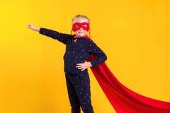 Menina pequena engraçada da criança do super-herói do poder em uma capa de chuva vermelha e em uma máscara Conceito do super-heró Foto de Stock Royalty Free